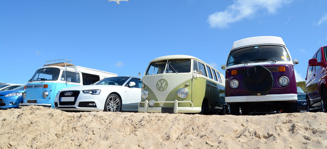 campervans and cars parked on a beach